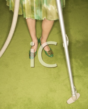 Royalty Free Photo of a Close-Up of a Woman's Feet With a Vacuum Against a Green Retro Carpet