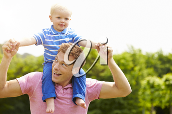 Father Giving Young Son Ride On His Shoulders In Garden