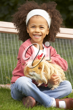 Young girl in garden holding guinea pig