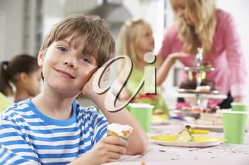 Group Of Children Enjoying Birthday Party Food At Table