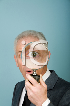 Royalty Free Photo of a Businessman With a Magnifying Glass