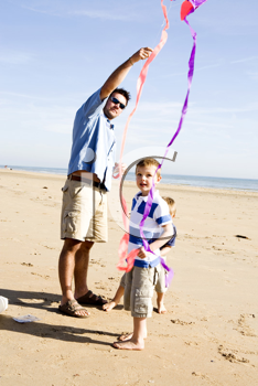 Royalty Free Photo of a Father and Son Flying a Kite on the Beach