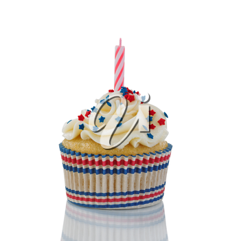 Close up image of Fourth of July decorated small cupcake with unlighted candle isolated on white with reflection.