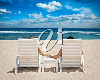 Honeymoon travel resort concept - couple in beach chairs holding hands near ocean