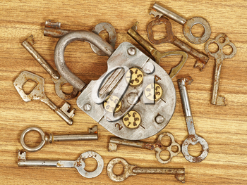 Old metal lock and keys on a wooden table background.
