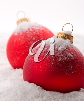 Red christmas baubles on snow