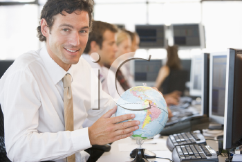 Royalty Free Photo of a Man With a Globe at His Computer