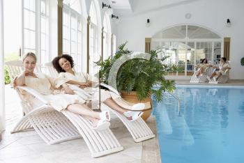 Royalty Free Photo of Women Relaxing Around a Pool