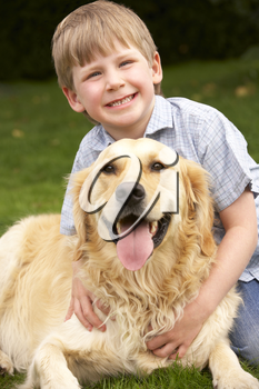 Young boy in garden with golden retriever