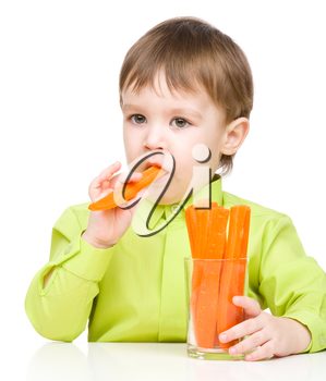 Little boy is eating carrot, isolated over white