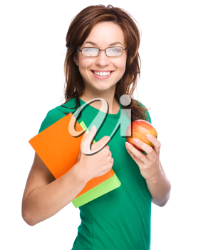 Young student girl is holding exercise book and apple, isolated over white
