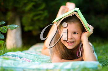Little girl is hiding under book while laying on green grass
