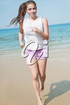 Attractive young woman running alone on the beach