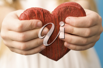 Close-up of red wooden heart in child's hands showing it